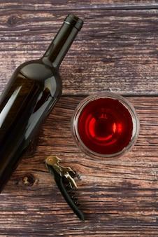 ワインと木製のテーブルの上のグラスの濃い瓶。コピースペース平面図。