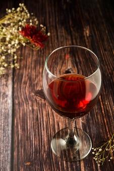 素朴な木製の織り目加工テーブルの上の赤ワインのガラス。