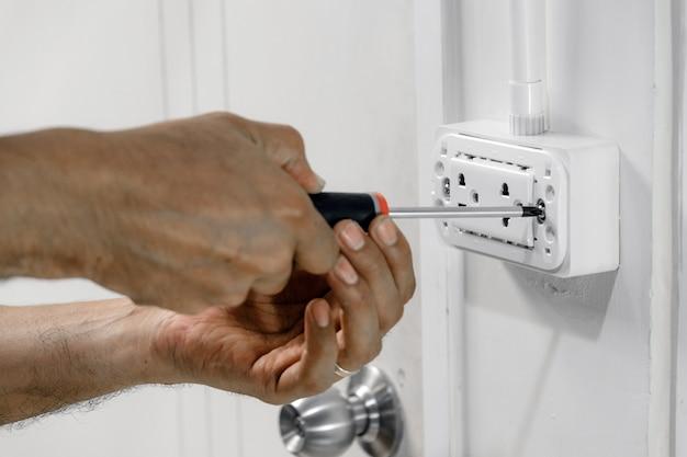 電気技師は、ドライバーを使用して電源コードを壁コンセントに接続しています。