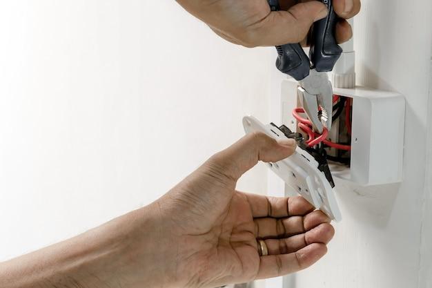 技術者は、電源プラグを壁に取り付けるためにペンチレンチを使用しています。