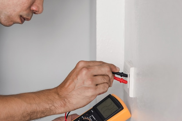 デジタルメーターを使用して、壁の電源コンセントの電圧を測定します。