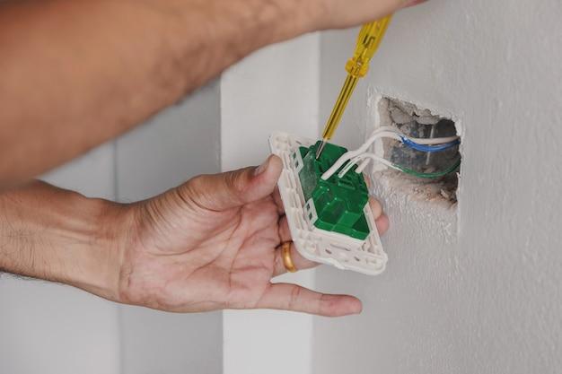 電気技師は、ドライバーを使って壁の電源プラグを確認しています。