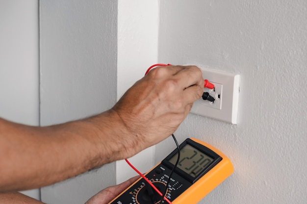 電気工事は、デジタルメーターを使用して電源コンセントの電圧を測定しています