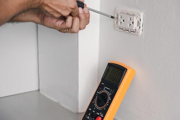 電気技師は、ドライバーを使用して電源コードを壁のコンセントに接続しています