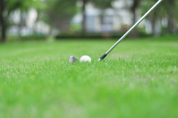 ゴルフ場の緑の芝生の上のゴルフボールにクローズアップ。