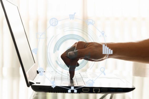 ビジネスマンのクローズアップ手はオフィスでスマートフォンやラップトップを使用しています。
