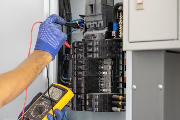 電気技師は、サーキットブレーカーのコントロールキャビネットの電圧を測定するためにデジタルメーターを使用しています