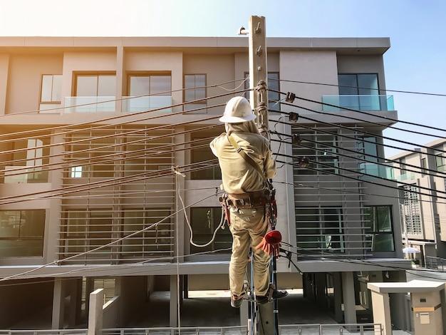 電気技師は電力線を取り付けるために電柱に登っています。