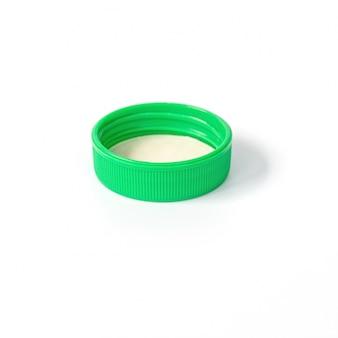 Зеленая пластичная крышка бутылки изолированная на белизне.