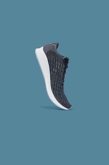 ファッションは、青に分離されたスニーカーの靴を実行しています。