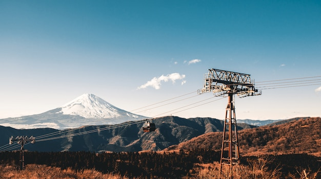 日本の冬の季節には、ケーブルカー、ティール、オレンジ色のトーンで雪に覆われた美しい富士山。