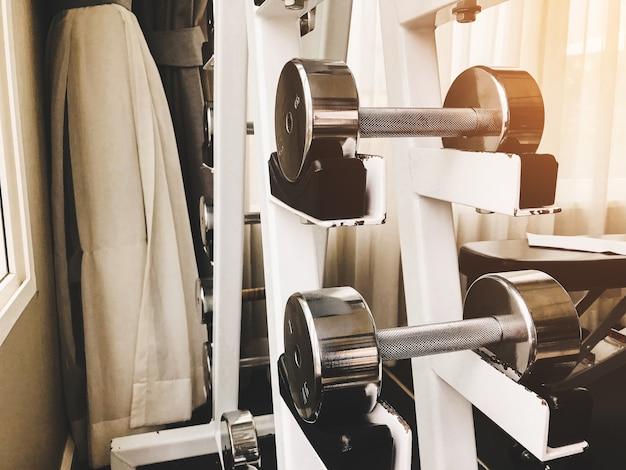 ダンベルのクローズアップグループは、ジムで腕の筋肉を行使するためのさまざまな重み。