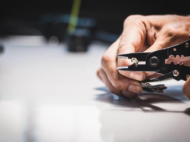 電気技師の手元のクローズアップは、産業用アプリケーションで電気ストリッパーを使用しています。
