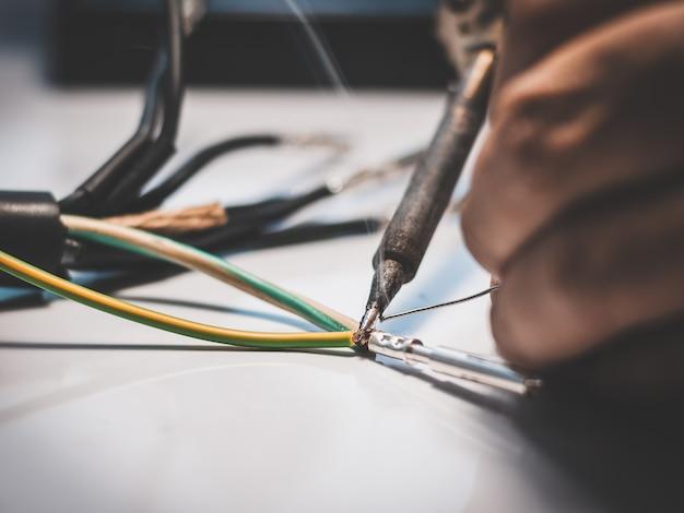 電気技師は、はんだごてを使用して、ワイヤをはんだピンで金属ピンに接続しています。