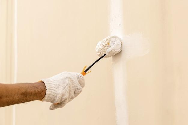 ローラーを使用してコンクリートの壁に白い色を塗る