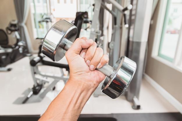 クローズアップ男の手は、ジム、運動と健康管理のための概念で彼の左手でダンベルを保持しています。