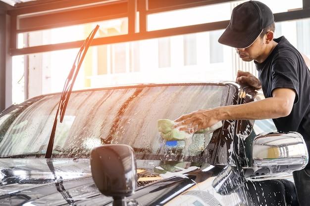 Работник автомойки с использованием губки для очистки автомобиля в центре автомойки.