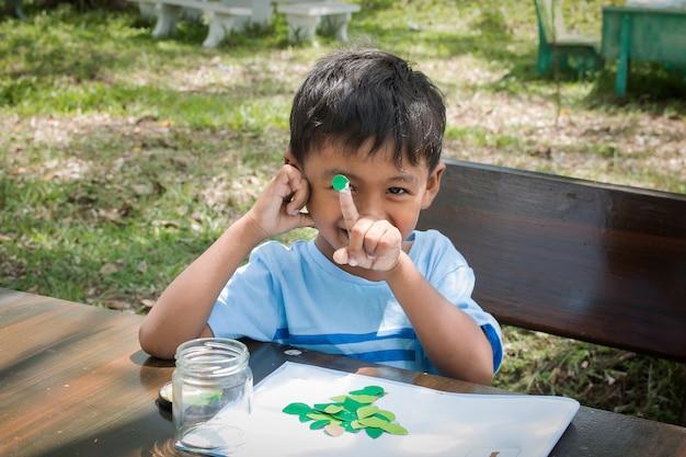 かわいい少年は緑の公園で宿題をする