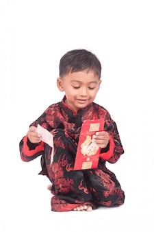 幸せな中国の旧正月、赤い封筒を保持しているアジアの小さな男の子