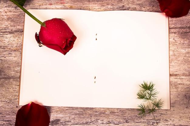 赤いバラの花とメモ帳の木製の背景を見る