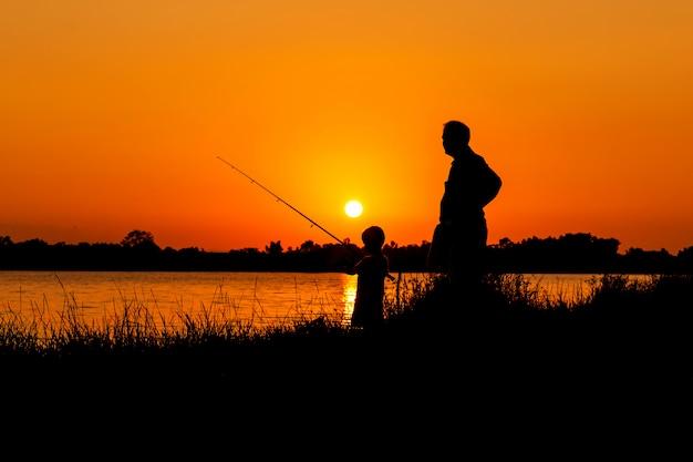 父と息子が川の夕日を背景に釣り