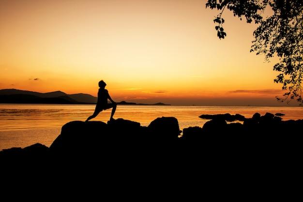 女性運動し、ビーチの夕日を背景にリラックス