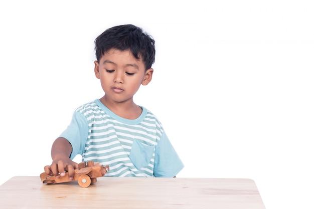 Мальчик милого ребенка азиатский играя деревянный самолет