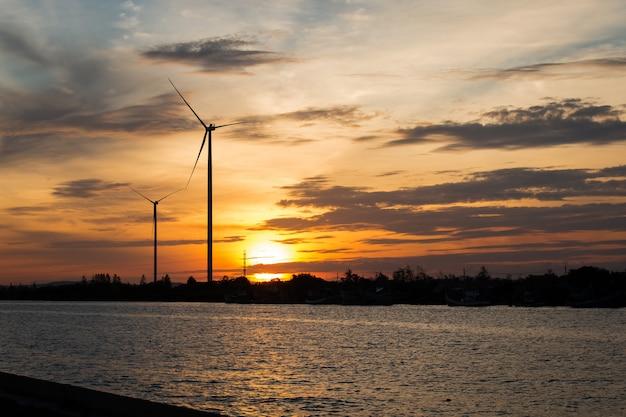 川の背景で風力タービンの夕日