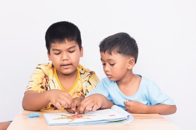 Два маленьких мальчика играют глину на книге на белом фоне