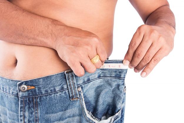 測定テープを持つ男の腹部