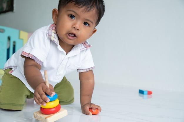 小さな男の子は部屋で木のおもちゃを遊ぶ