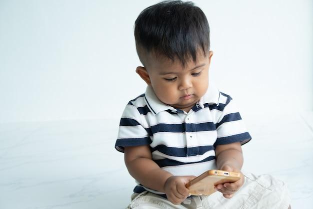 かわいい小さなアジアの男の子がスマートフォンをプレイ