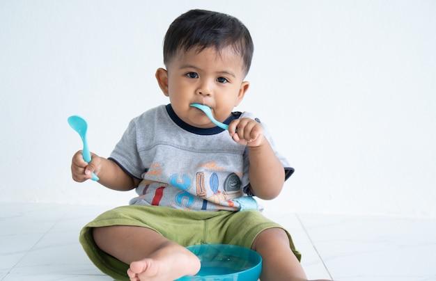 Милый маленький мальчик асин с ложкой