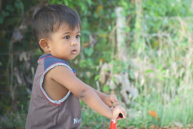 Мальчик играет на велосипеде, используя вспаханную ногу - велосипед