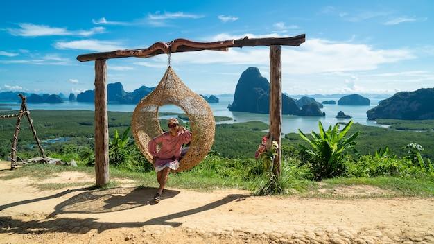 山の頂上から渓谷の景色を楽しんで幸せな若い女性
