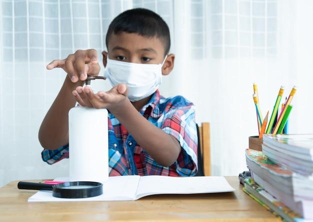 かわいいアジアの少年が消毒剤で手を洗う