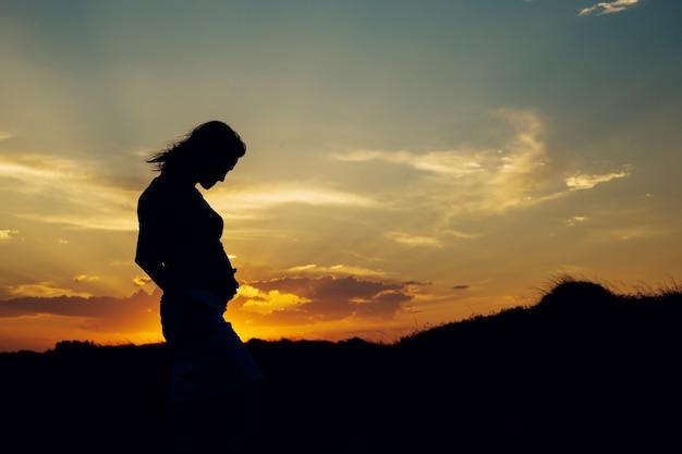 自然の背景と夕日のバックライトと自然の妊娠中の女性の腹の写真