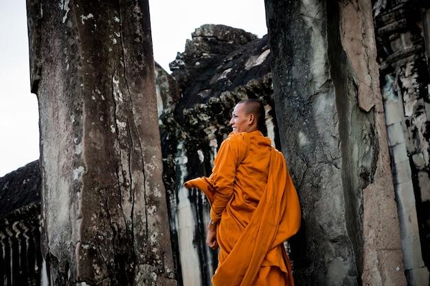 チベットの僧侶たちは遠隔のカンボジアの寺院を訪れて黙想するオレンジ色の服を着た。