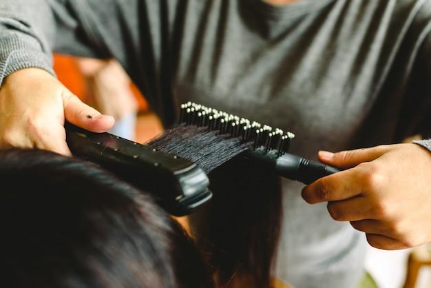 ヘアストレートナで女性の髪を平滑化する美容師。