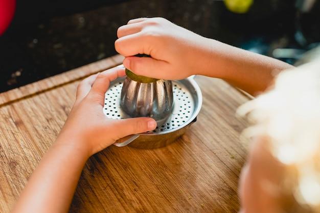 レモンのジュースを絞る子供。