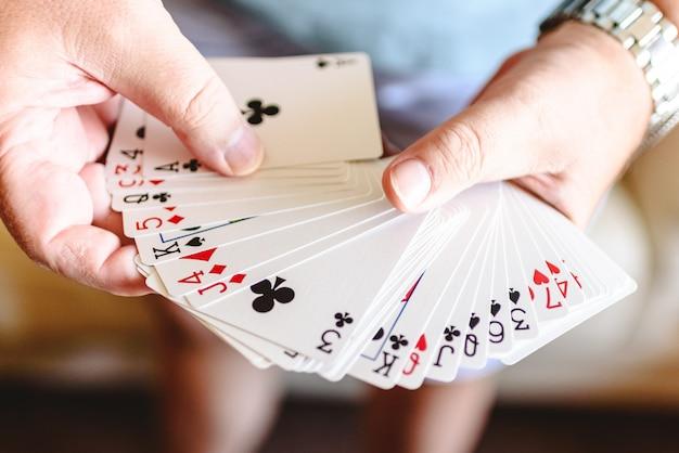 マジシャンの手はカードで魔法のトリックをしています。