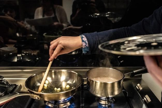 シェフが鍋にシチューをかき混ぜる。