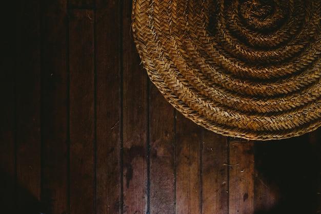 木製の床の背景に円形の籐マット、上からの眺め。