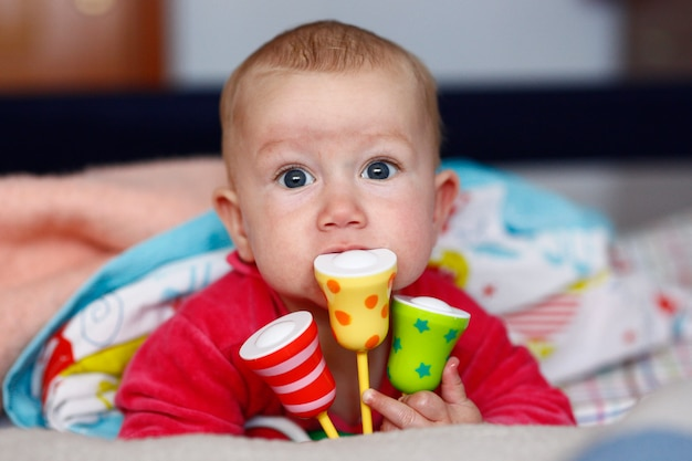 彼女のガラガラをかみながら遊ぶかわいい赤ちゃん