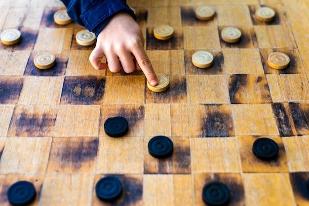 子供の手がチェッカーゲームのピースを動かす、闘争の概念