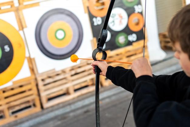 公正でブルズアイでトレーニング弓を目指している少年。