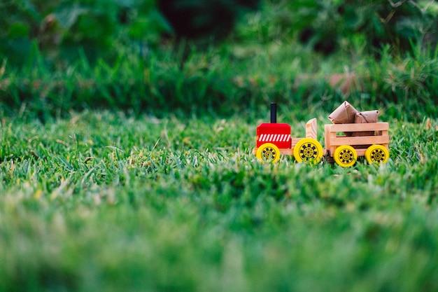 芝生や自然を通してパッケージを運ぶ木のおもちゃのトラック