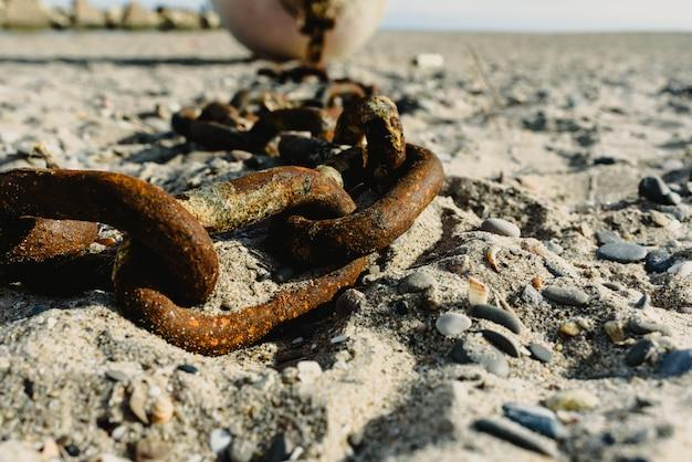 Концепция брошенных, старых ржавых и сломанных цепей, брошенных в песок грязного пляжа.