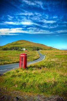 道路の近くの農村地域での典型的な赤い英語電話ボックス。