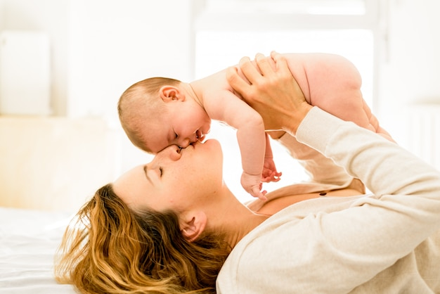 ママは愛情を込めて彼女の新しく生まれた娘、母性および幸せな家庭生活の概念にキスします。
